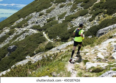 fast running man with compress socks and backpack on high mountain alpine trail in alps