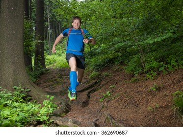 fast running man on the muddy trail in the morning spring dark forest