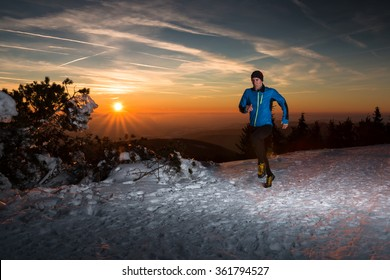 fast running man on the winter track with snow and beautiful sunset