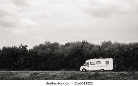 Fast RV camer van driving on the green dunes in Netheralnds during Euroeapn holidays - black and white