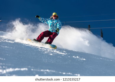 Fast snowboarder downhill at ski slope. Snowboarding concept