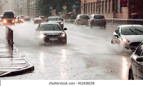 Fast speed. Moving car sprays puddle when heavy rain drops on concrete. Wide screen