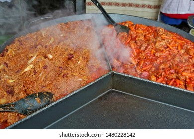 Fast street-food - smoked pork  meat with  fried carrots and  rice  in big iron black frying pan. Snapshot style image