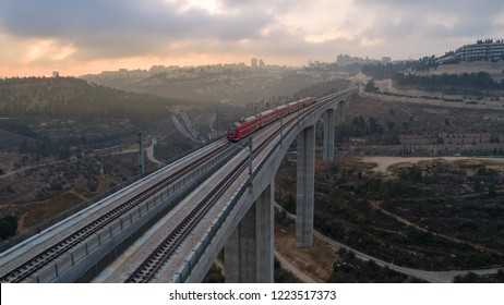 The fast train connecting Jerusalem to Tel-Aviv, crossing over a valley bridge at dawn.