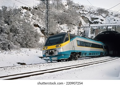 Fast train, express drive out from a tunnel in winter