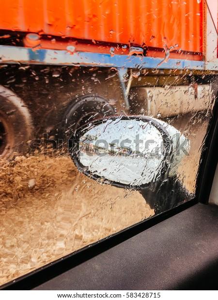 Fast truck splash water on car side window.