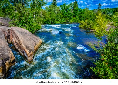 Fast wild water in wilderness river, rushing through granite walls and surrounded by forest vegetation.