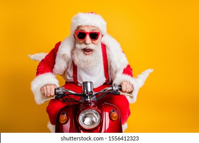 Fast x-mas traveling! Crazy funky hipster grey haired santa claus in red hat drive scooter hurry scream wear shirt suspenders isolated over bright color background