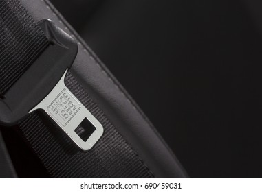 Fasten seat belt. A macro shot of a brand new seatbelt isolated on black. The belt is composed to the left. Copy space. Since 1959 text on the metal