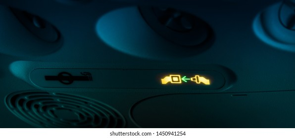 Fasten your seat belts blinking icon announcement on small air plane night flight or when flying in turbulences area. Blurry yellow green Buckle up sign on dark black blue airplane interior background