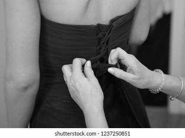 Fastening back of bridesmaid dress close up