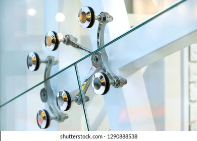 Fastening of glass walls. Architecture abstract background. Glass curtain walls. The elements of the fastener system metal glass spider. Front Windows