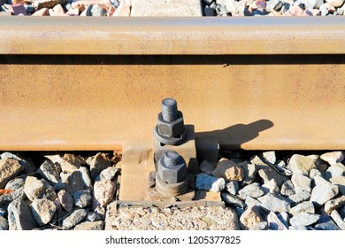 Fastening the rail to the sleepers with bolts.