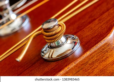 Fastening of a string on an acoustic guitar. Macro shooting