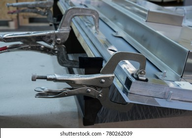 Fastening of two surfaces on a carpenter's table with the help of a clamp for reliable gluing of two dissimilar surfaces in the process of individual furniture production