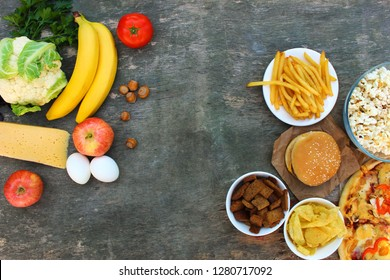 Fastfood and healthy food on old wooden background. Concept choosing correct nutrition or of junk eating. Top view.