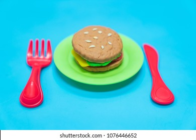 Fastfood model with hamburger chesse on plastic blue table background, play dought at home, child care cooking food model, educational toys for kid creative for toddlers concept.