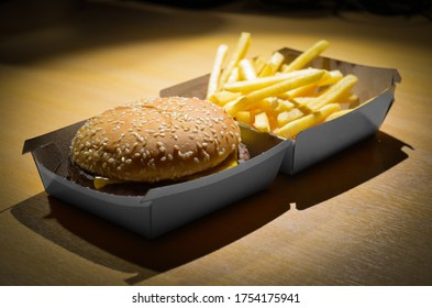 A fast-food restaurant hamburger. Fries behind with a slight out of focus to subtract protagonism.