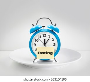 fasting time, alarm clock on white plate