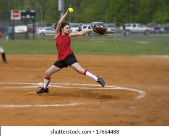 a fastpitch softball player pitching the windmill