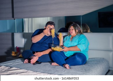 Fat Asian couple eating instant fried noodle gluttonously, while watching television in their bedroom