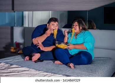 Fat Asian couple gaping at instant fried noodle gluttonously, while watching television in their bedroom