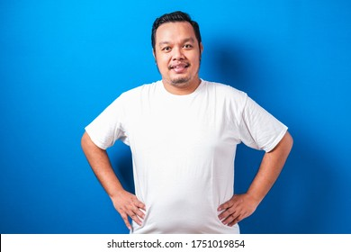 Fat Asian guy wearing a white T-shirt stands by placing his hands on his waist smiling toward the camera. The man shows confident gesture, against blue background.