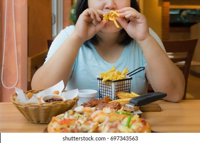 fat asian woman is eating french fries and fast food, overweight female have unhealthy foods