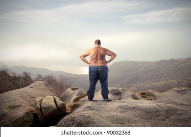 Fat bare-chested man in the mountains