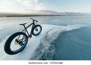 Fat bike (also called fat bike or fat-tire bike) - Cycling on large wheels. Bicycling is at sunset on the ice.