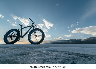 Fat bike (also called fat bike or fat-tire bike) - Cycling on large wheels. Bike stands on the background of sunset on ice.
