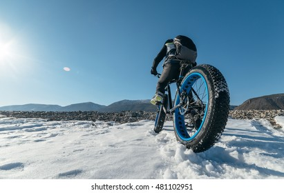 Fat bike (also called fat bike or fat-tire bike) - Cycling on large wheels. Teen rides a bicycle through the snow mountains in the background.
