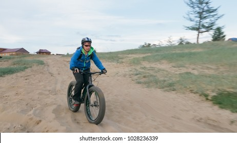 Fat bike also called fatbike or fat-tire bike in summer driving through the hills. The guy is riding a bike along the sand and grass high in the mountains. He performs some tricks and runs dangerously