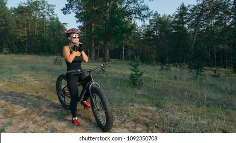 Fat bike also called fatbike or fat-tire bike in summer riding in the forest. Beautiful girl and her bicycle in the forest. She rolls her bike and poses to the operator.