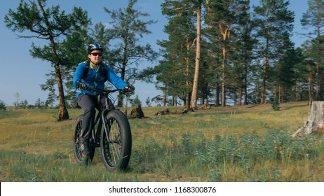 Fat bike also called fatbike or fat-tire bike in summer riding in the forest. The guy rides a bicycle among trees and stumps. He overcomes some obstacles on a bumpy road.
