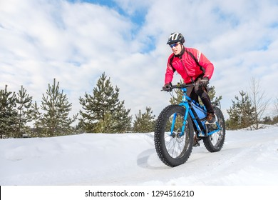 Fat biker riding his bicycle in the snow during winter. Fat bike.