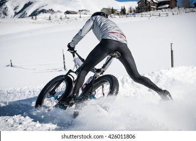 Fat biker skids around corner in snow.