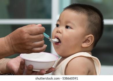 Fat boy eating.Hand holding a spoon feeding children.