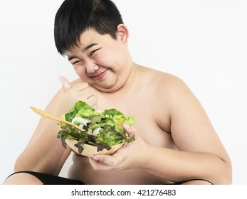 A fat boy is happily eating vegetable salad