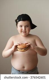 fat boy holding a hamburger and smiling