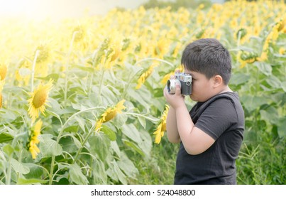 fat boy holding vintage camera / Child Holding old camera to Take Photos sunflower flower