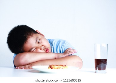 The fat boy looks at the pizzas on a white table with a glass of water in his mouth.