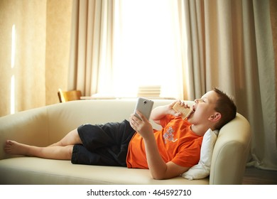 fat boy is lying on the couch playing with the phone in the room in an orange shirt is eating ice cream