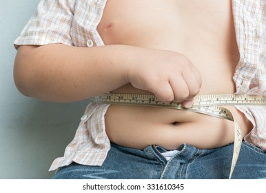 fat boy measuring his obese on gray background