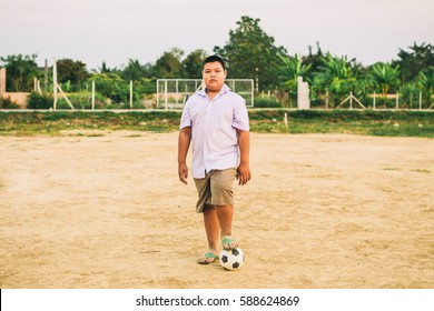 A fat boy playing soccer football for exercise which is a good for children to decrease the overweight or obese.