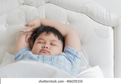fat boy sleep on white bed