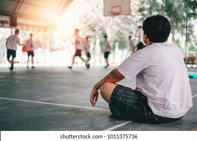 Fat boy student watching his friends play basketball at the gymnasium in school.
