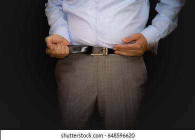 Fat business man. Do not close the belt. Tight pants