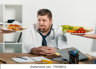 fat businessman choosing healthy or junk food at workplace in office