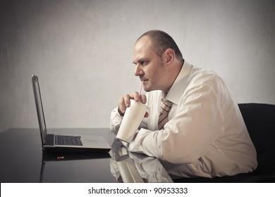 Fat businessman drinking a sparkling beverage